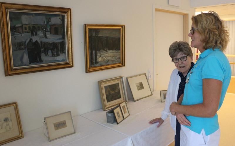Siv Lindblad och Annelie Maars, som ansvarade för det praktiska vid överlämnandet, tittar på Carlbergs målningar.
